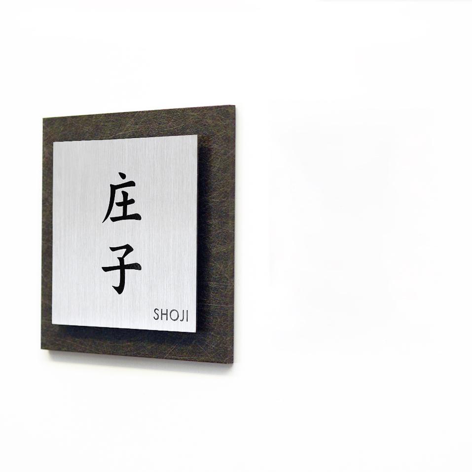 老舗料亭のようなシックで格式高いデザインのアクリル表札を白い壁にセットした画像