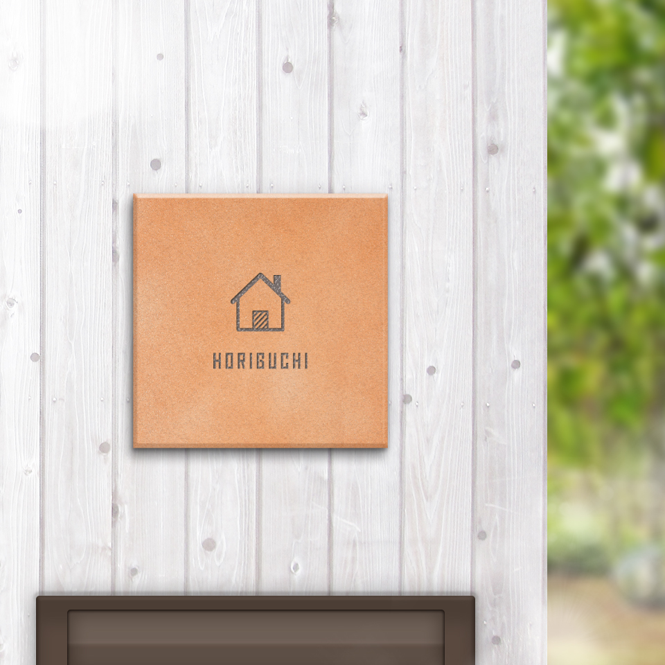 アットホームな印象の玄関になるデザインのタイル表札を白い木の壁にセットした商品画像
