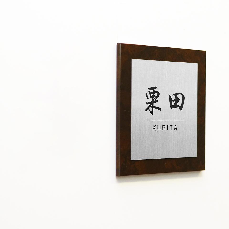 額縁に収められたようなデザインのアクリル表札を白い壁にセットした商品画像
