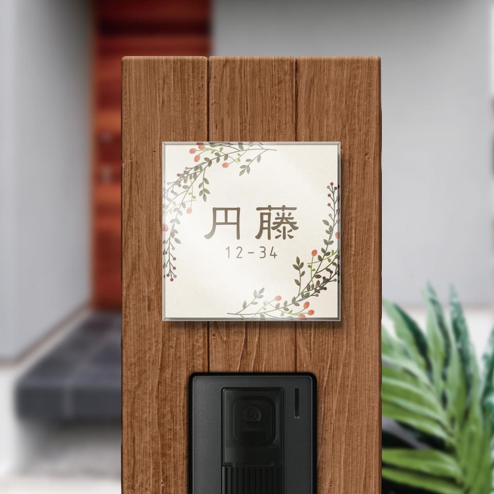 ナズナのイラストデザインのアクリル表札を木目の壁にセットして撮影した画像