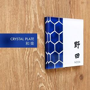 かっこいいと人気の藍色甲羅模様デザインのおしゃれアクリル表札を木目の壁にセットして撮影した画像