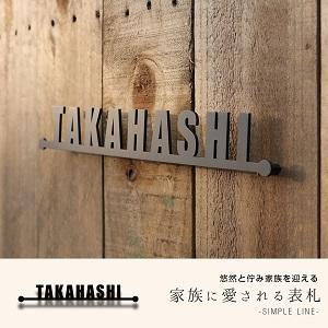 シンプルなデザインで人気の格安おしゃれ表札を木目の戸建て壁にセットして撮影した画像