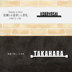 黒の壁に映えるシンプルデザインの白色ステンレス表札デザイン例画像
