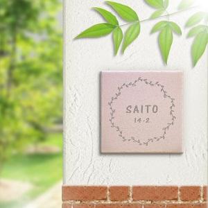 シンプルな草木冠デザインのタイル表札を白い壁にセットした商品画像