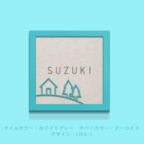 家のラインアートが入ったフレーム付きタイル表札を水色の壁を背景に撮影した商品画像