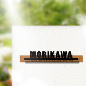 木目でアクセントをつけたシンプルデザインのアイアン・ステンレス表札を白い壁にセットしたデザイン例