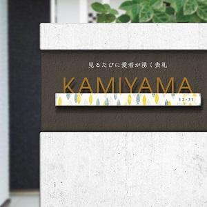 シンプルな文字に葉のテクスチャーアクセントを入れたデザインのアイアン・ステンレス表札を黒い壁にセットしたデザイン例