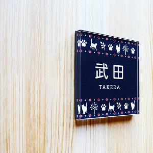 猫や肉球アイコンを使って大人っぽくデザインしたアクリル表札を木目の壁にセットした画像