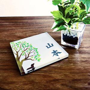 ダックスフンドが木の下に佇むデザインのアクリル表札を木目の壁にセットした画像