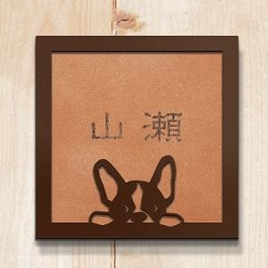 フレンチブルドッグが顔を覗かすかわいいデザインのタイル表札を木目の壁にセットした商品画像