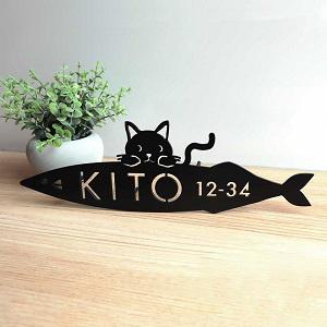 お魚くわえた猫をデザインしたアイアン・ステンレス表札を木目の壁を背景に撮影した画像