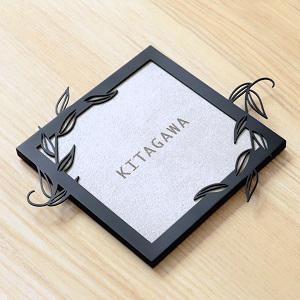 葉のつたが飛び出すデザインのフレーム付きタイル表札を木目を背景に撮影した商品画像