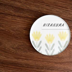 麦のイラストを北欧風にデザインしたアクリル表札を木目の壁を背景に撮影した画像