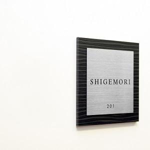 ゼブラ調が額縁がモダンなデザインのアクリル表札を白い壁にセットした商品画像
