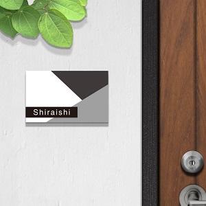 白い壁に置いたモノクロデザインのアクリル表札