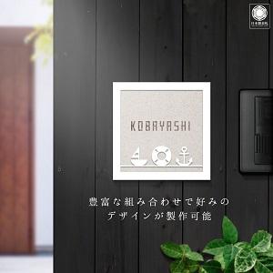 マリーンパーツをフレームにおさめたデザインのタイル表札を黒い壁にセットした商品画像