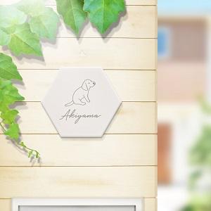手書き風の犬イラストが入ったデザインのタイル表札を木目の壁にセットした商品画像