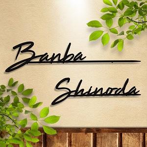 アルファベット筆記体デザイン表札を漆喰の壁に植物と合わせて設置した2種類のデザイン例