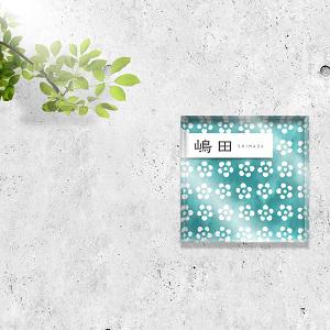 梅の水彩柄デザインのアクリル表札をコンクリートの壁にセットした画像