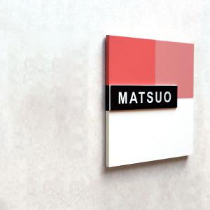 赤の明度差を使った柔らかいデザインのアクリル表札を白い壁にセットした商品画像