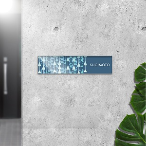 大人っぽいおしゃれ感のある木の短冊デザインをしたアクリル表札をコンクリート壁にセットした画像