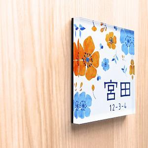 華やかな花パターンデザインのアクリル表札を木目の壁にセットした画像