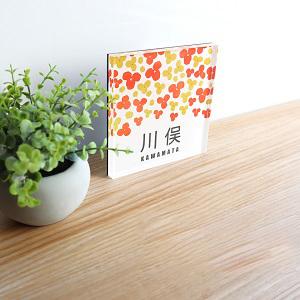 花びら3枚の小さな花を散りばめたデザインのアクリル表札をデスク上に置いて撮影した画像