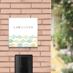 生地のパターンデザイン風アクリル表札をタイル調の壁にセットした画像