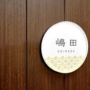 風水に良い金色の渦巻き模様デザインのアクリル表札を木目の壁にセットした画像