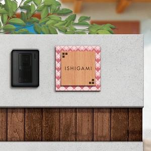 華やかでアクセントのあるデザインのアクリル表札を白壁にセットした商品画像