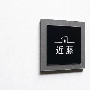 シンプルなハウスデザインのタイル表札を白い壁に設置した商品画像