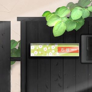 梅柄に新鮮なイメージを感じさせるカラーリングの和風おしゃれ表札を黒い壁にセットした画像