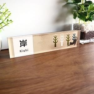 落ち着いた色合いと特長的なフォントがおしゃれなデザインのアクリル表札を木目の壁にセットした画像
