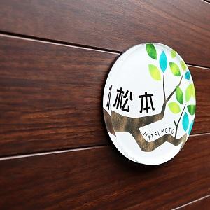 メルヘンタッチの影絵調デザインのアクリル表札を木目の壁にセットした画像