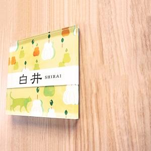 洋梨と猫イラストがカワイイデザインのアクリル表札を木目の壁にセットした画像