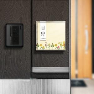手書き風猫イラストがアットホーム感を出しているデザインのアクリル表札を木目の壁にセットした画像