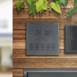 落ち着いた渋いデザインのタイル表札を木目の壁に設置した商品画像