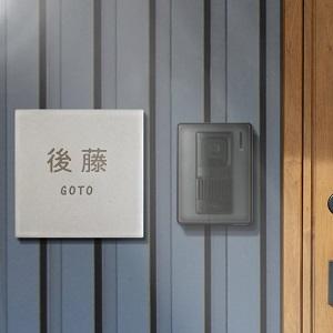 シンプルデザインのホワイトグレー色タイル表札を黒い壁に設置した商品画像