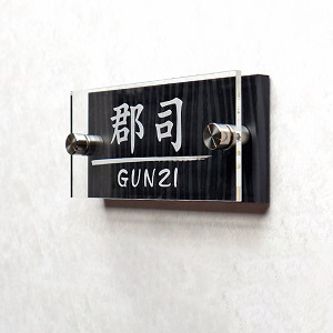 かっこいいブラックカーボンが印象的なアクリル表札を白い壁にセットした画像