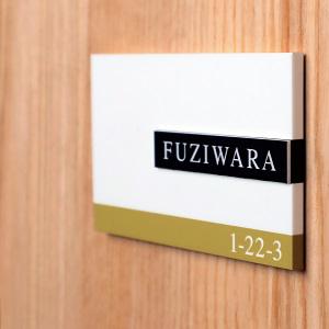 シンプルですっきりとしたデザインのアクリル表札を木目の壁にセットした商品画像