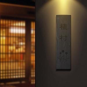 味わい深いデザインの縦書きタイル表札を黒い壁に設置した商品画像