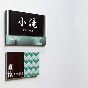 グリーンのベースカラーで和モダンデザインのアクリル表札を白い壁にセットした商品画像