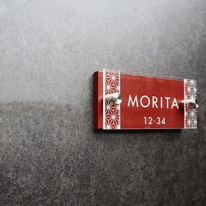赤のレザー調と麻の葉文様が印象的なデザインのアクリル表札を黒い壁にセットした画像