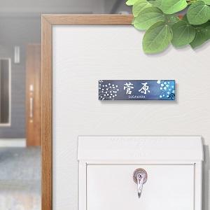 夜空に映えるアニメ風イラストデザインのアクリル表札を門柱に設置した画像