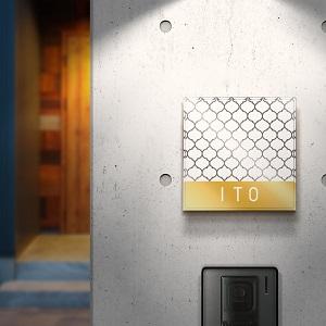 モダンな雑貨風網目デザインのアクリル表札をコンクリートの壁にセットした画像