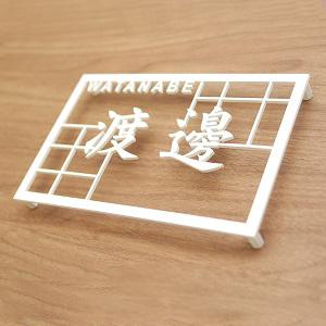 格子模様と漢字が絡んだデザインのアイアン・ステンレス表札を木目の壁にセットしたデザイン例