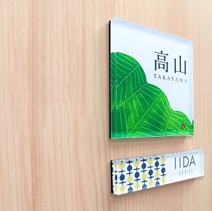 緑の葉と白の余白がすっきりとしたデザインのアクリル表札を木目の壁にセットして撮影した画像
