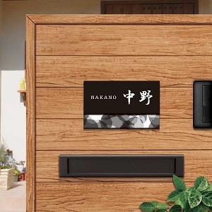 モノクロでモダンなデザインのアクリル表札を木目の壁にセットした商品画像