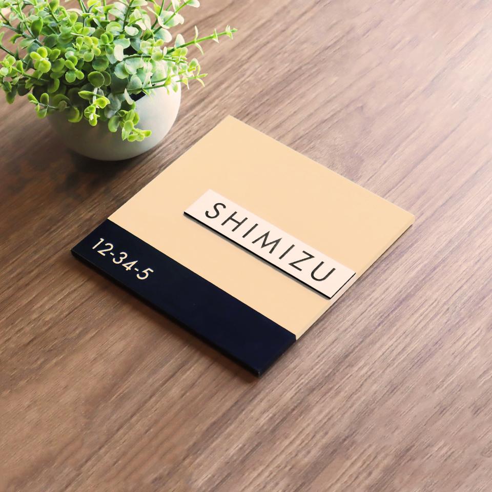 やわらかく化粧品ブランドのようなデザインのアクリル表札を木目板に置いて撮影した画像