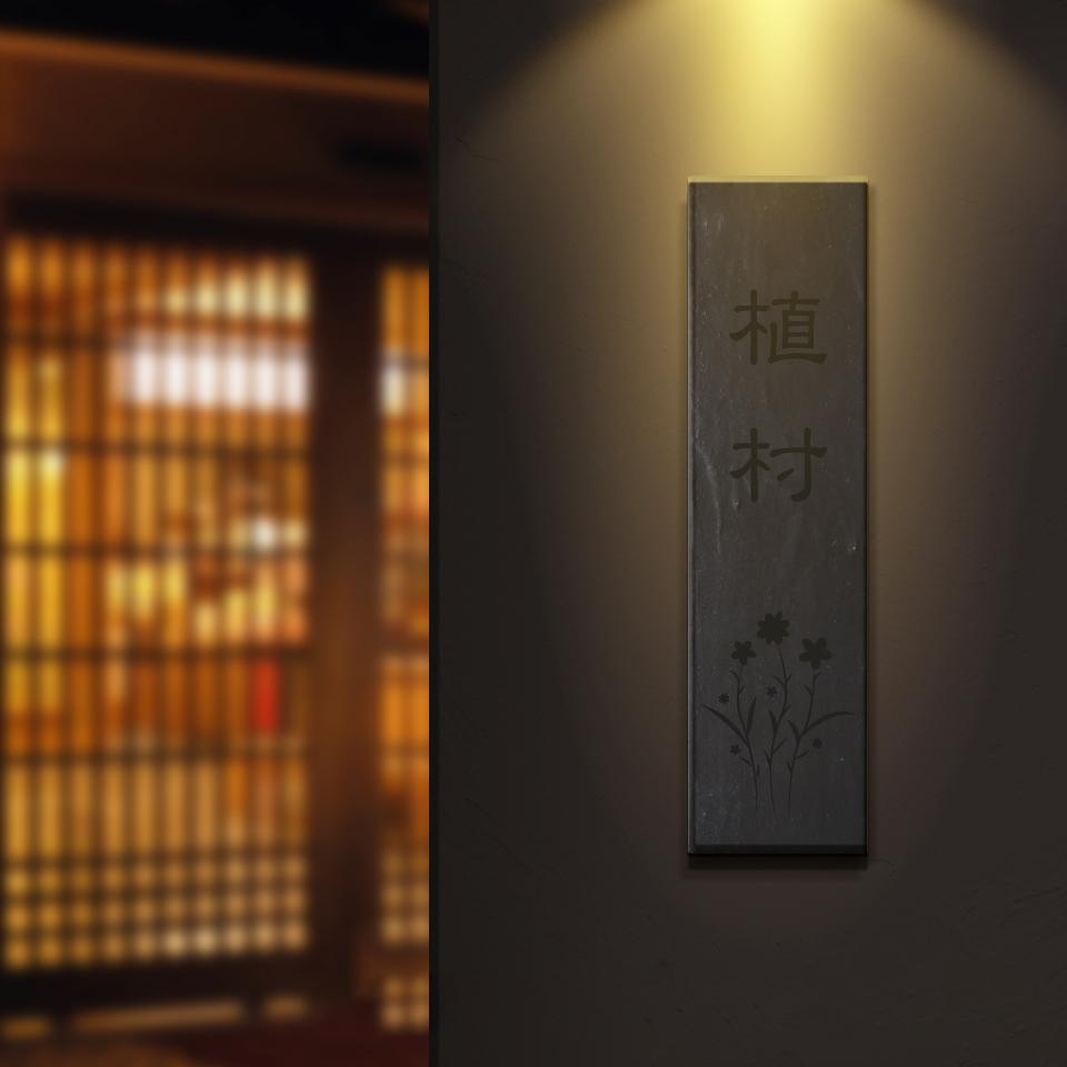 味わい深いデザインの縦書きタイル表札を黒壁に設置した写真